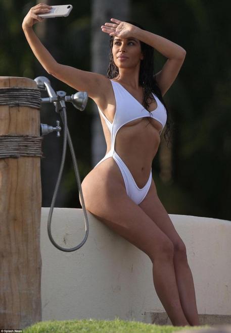 ... φορώντας ένα λευκό μαγιό που αφήνει ελάχιστα στη φαντασία. Το επάνω  μέρος του μαγιού μετά βίας συγκρατούσε το πληθωρικό μπούστο της. ΜΑΓΙΟKim  Kardashian e10a03bf22d